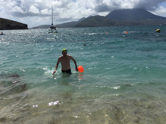 Jim Nostrum comes ashore on St. Kitts after swimming from Nevis in the background.